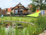 """Die """"Quelle"""" liegt im Parterre des Hauses. Hier vom Schwimmteich aus gut zu sehen die große Hochterrasse der Quelle. Rechts im Bild übrigens die Gartensauna!"""